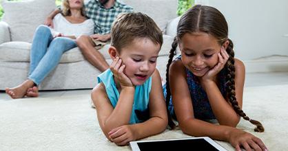Dos niñas pasan tiempo frente a la pantalla en casa mientras los padres observan.