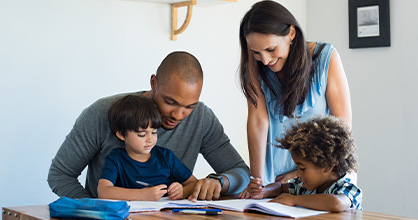 A mixed-race family sits around a table doing homework.