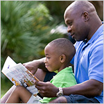 Father reading a book to his young son in the park.