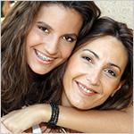 Hija adolecente abrazando a su mam__ ambas sonrientes