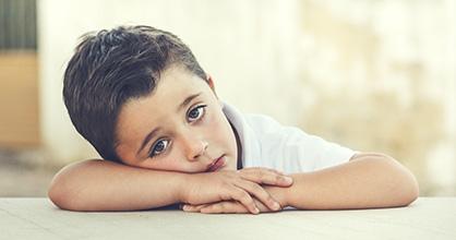 Un niño pequeño, aburrido, apoya la cabeza sobre sus brazos.