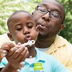 Pap_ e hijo soplando burbujas en el parque.