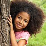 Shy little girl peering out from behind a tree.