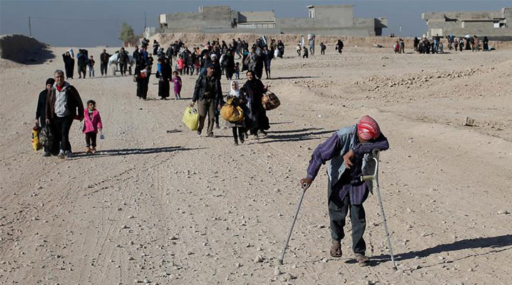 Refugees carrying possessions flee fighting, walking down a dry dirt road. One man on crutches pauses to rest, with one arm draped over one of his crutches and his head resting on his arm face down.
