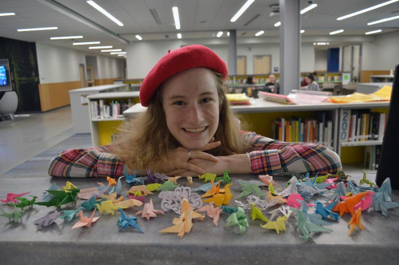 Patricia Morris with some of her tiny origami dinosaurs