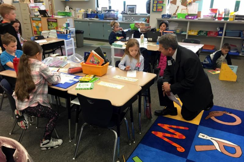 Tony Giurado talks with a student in Kelly Minniti_s first grade classroom