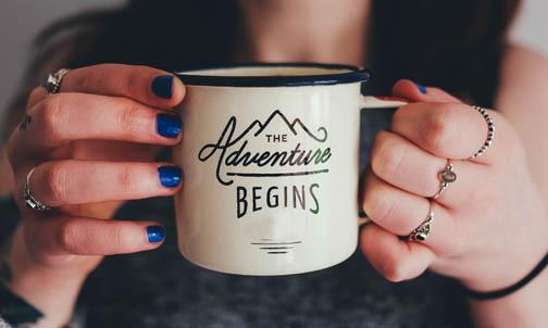 the next adventure begins written on coffee mug woman is holding