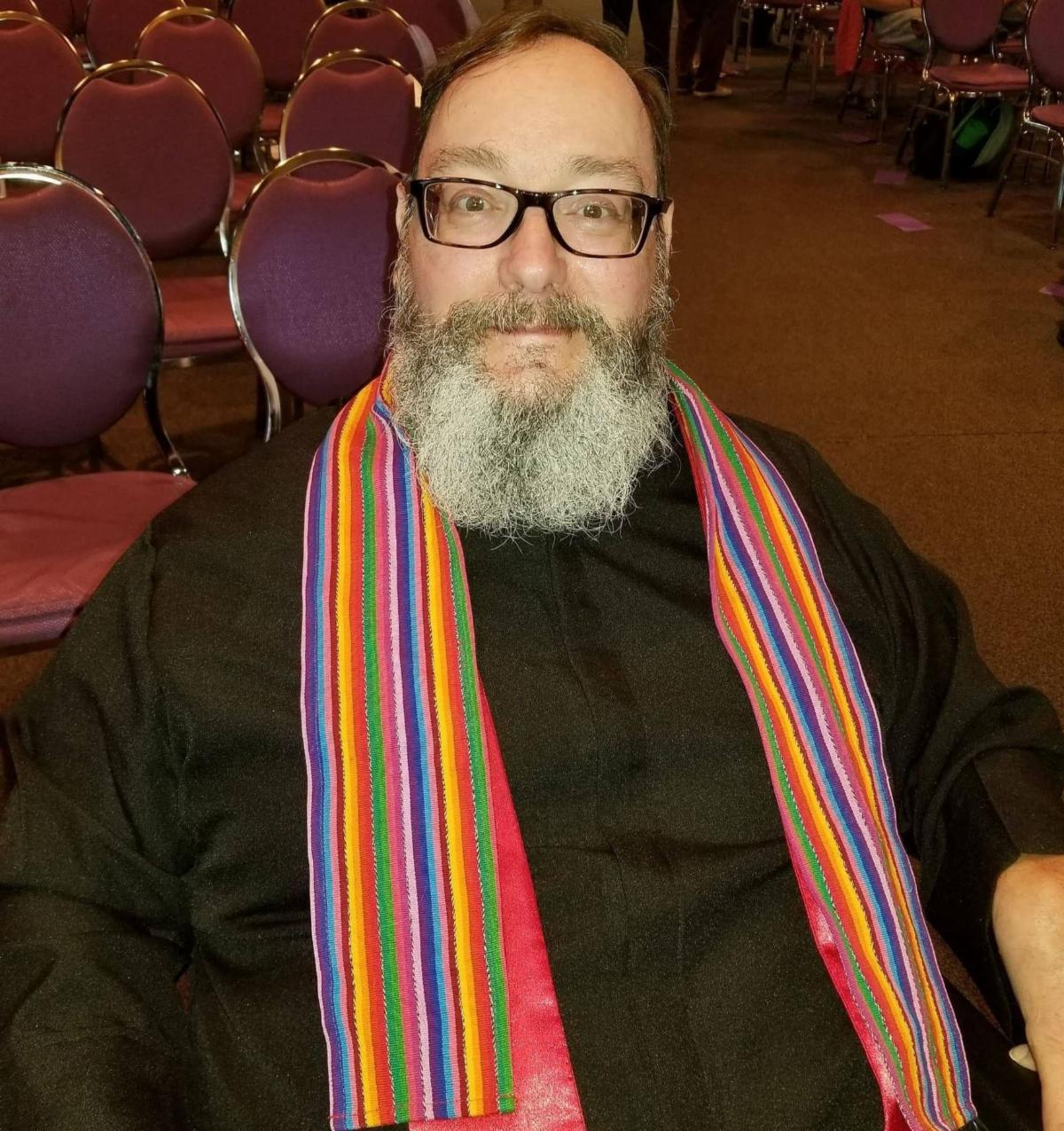 Chris sits in his wheelchair_ wearing a black clerical robe and rainbow stole.  He wears glasses and has a moustache and graying beard. Rows of empty chairs are in the background.