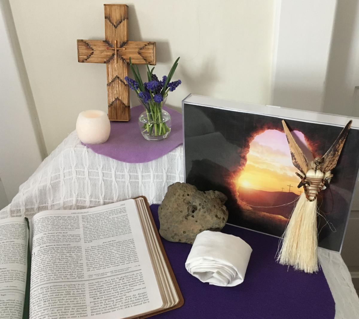 Home altar with matchstick cross_ battery candle_ bouquet of grape hyacinth flowers_ open Bible_ stone_ rolled white cloth_ crafted angel_ and photo taken from inside an empty tomb with three crosses silouhetted in the sunrise.