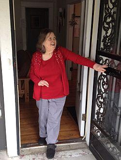A short woman opens a wrought iron screen door and smiles