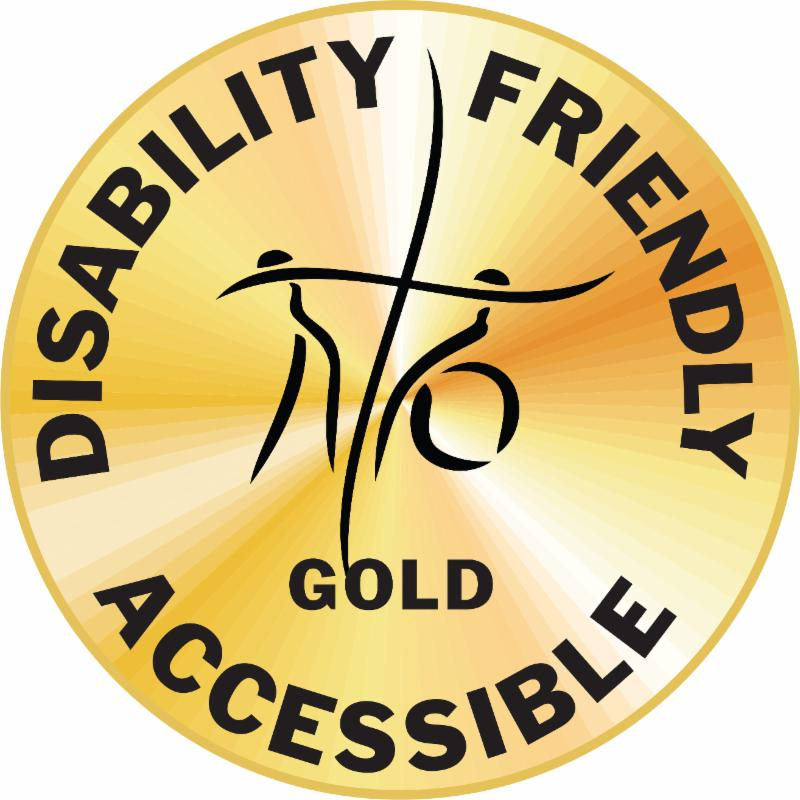 On a gold circle the words Disability-Friendly and Accessible surround the stylized standing person and person seated in a wheelchair whos arms form the horizontal bar of the cross in the DMC logo. The word Gold is below the logo