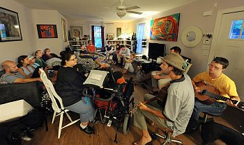 A diverse group of students and residents play guitar and other musical instruments during worship in a Friendship House apartment living room