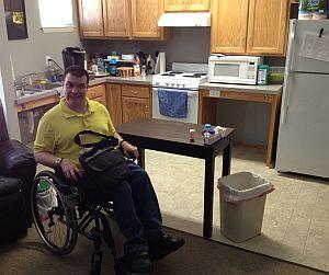 Man in wheelchair with his accessible apartment kitchen behind him