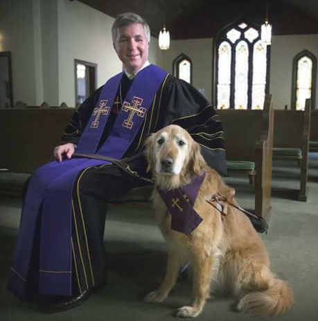 Pastor seated in pew wearing black robe and long purple stole next to his Golden retriever guide dog wearing a purple liturgical scarf as collar