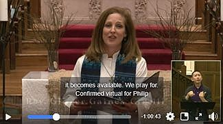 Still shot of video clip with female pastor standing in front of an altar_ a captioning bar in the lower part of the screen_ and an inset box showing a sign language interpreter.