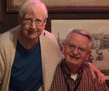 Carrie White with short white hair_ glasses_ and dangling bead earrings stands with her arm around seated Roy White_ in glasses and a red plaid shirt.  Both are smiling. A historic photo is in the background - a restaurant decoration.