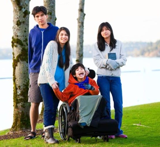 Three teen siblings stand behind a younger brother who uses wheelchair and has a big smile on his face as he holds a sister_s hand