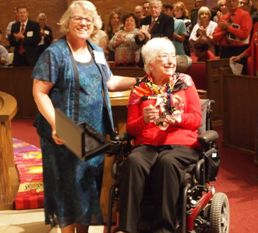 Woman in power wheelchair smiling as standing woman holds the award.  The congregation members behind them are standing and applauding.