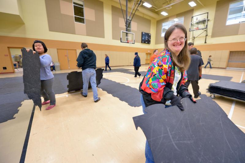 Two women hold pieces of protective floor tiles they are putting away in the church gym