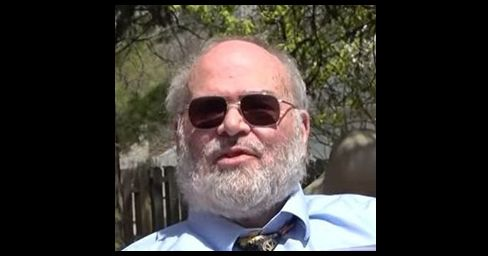 Man with grey hair and beard wearing sunglasses and a shirt with tie with greenery behind him.