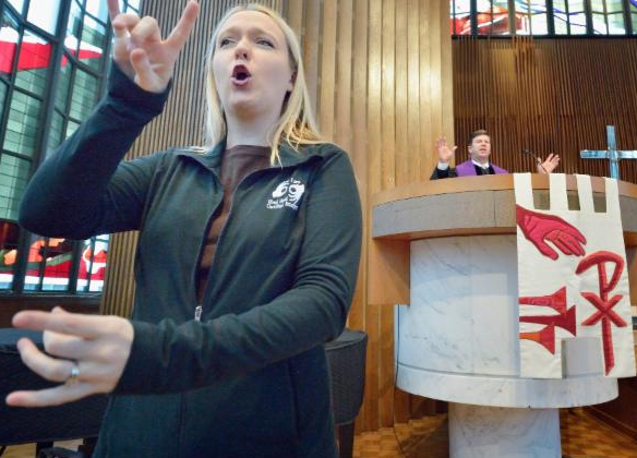 Interpreter in grey suit uses both hands and her facial expression to convey a concept. Pastor preaches from large white podium hung with red liturgical symbols on a banner
