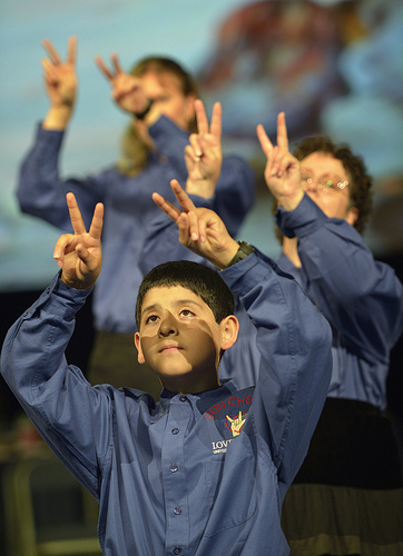 Three choir member in blue shirts hold both hands up with fingers making a V shape