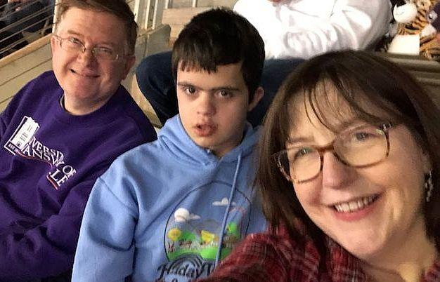A selfie of Brad_ Kyle_ and Beth at a ball game. Kyle_ in a hoodie sweatshirt_ looks intensely toward the camera.
