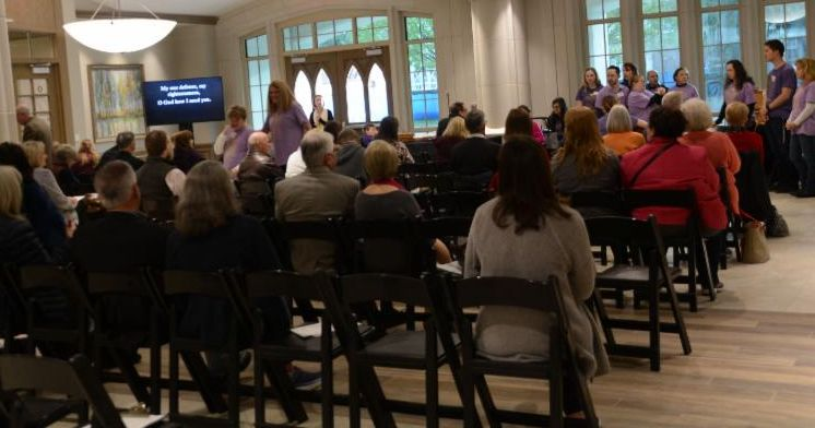 View from the back of rows of persons seated in folding chairs while the choir in purple T-shirts are in the front of the worship space. Arched windows in exit doors help transform the room into a worship space