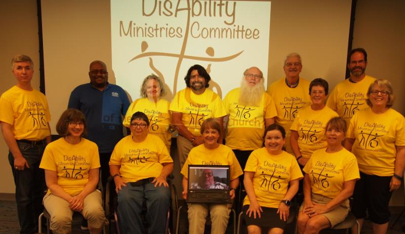 Members of the DMC in their yellow T-shirts with the committee logo projected behind them