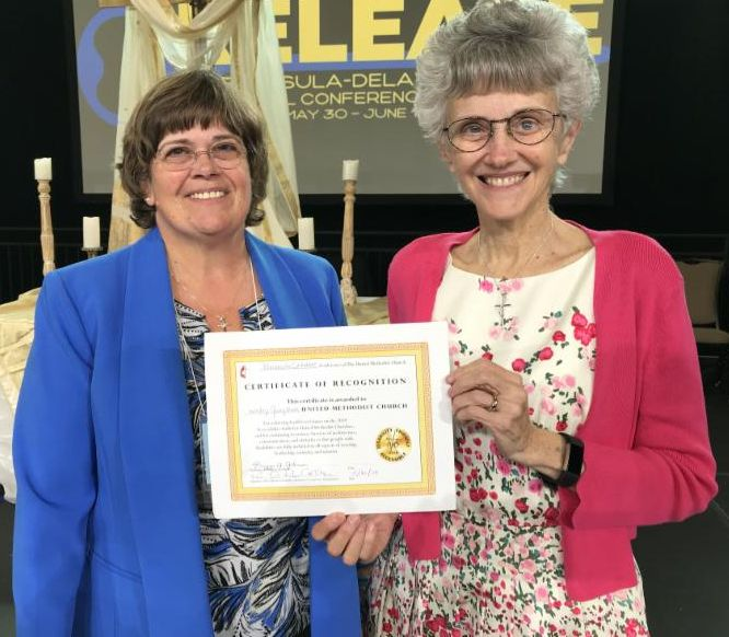 A woman in a blue blazer stands next to a woman in a pink sweater and floral dress who is holding the gold badge certificate. Annual conference decor is in the background