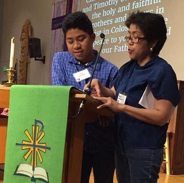 Youth stands behind lectern and reads scripture with his mom_s support. Both have brown skin and black hair reflecting their Filipino heritage