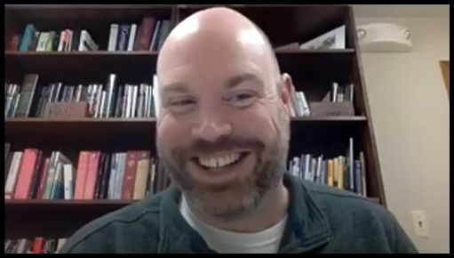 Smiling man with beard and mustache but no hair sits in front of a full bookcase.