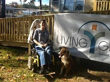 Woman in wheelchair with pet dog sits in front of ramp and sign that reads Living Grace UMC