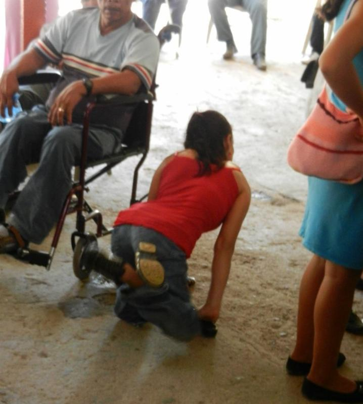 Woman on her hands and knees crawls next to a man seated in a wheelchair
