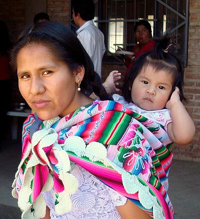 Woman in colorful ethnic cloth wrap that also holds her baby on her back