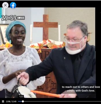 Screenshot shows worship leader Naomi in blue scarf and while blouse smiling while Pastor Tom in clerical garb and face mask with transparent mouth piece hitting a drum
