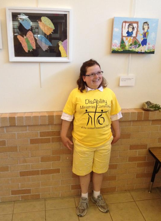 Short woman with big smile wearing the yellow committee T-shirt with 2 paintings of angels behind her