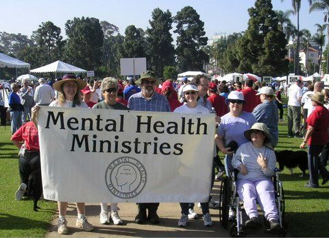 Four persons including Susan stand behind a Mental Health Ministries banner and two women including one in a wheelchair stand next to it with a crowd on the lawn behind them