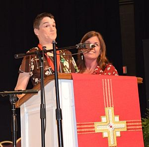 Christy and friend standing at microphone with cross on fabric banner on the lecturn front