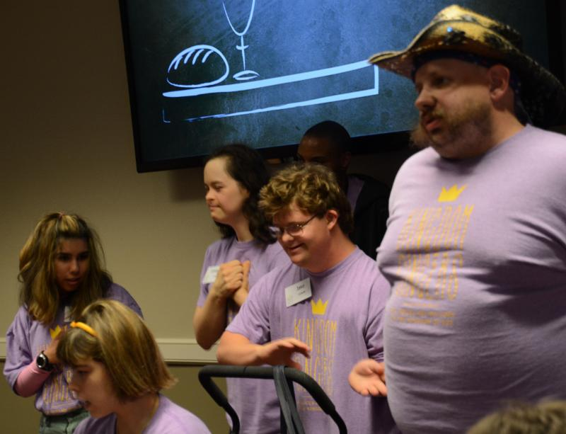 One male and three female choir members in purple T-shirts lead singing and signing