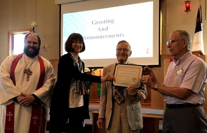 Male bearded pastor wearing white robe_ red stole_ and wooden cross stands next to Lynn in black sweater and deaconess scarf handing certificate to two men
