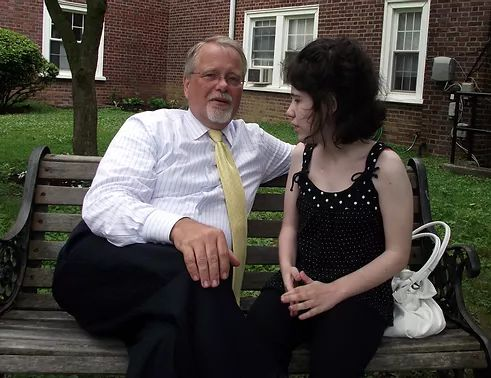 Sitting on a bench in front of a brick building Jim has a neat gray beard_ wears a white shirt with yellow tie. Lindsay has shoulder length dark brown hair and the top of her black formal has white polka dots.