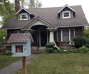 An older two-story house with 2 dormers and a little library in front of it