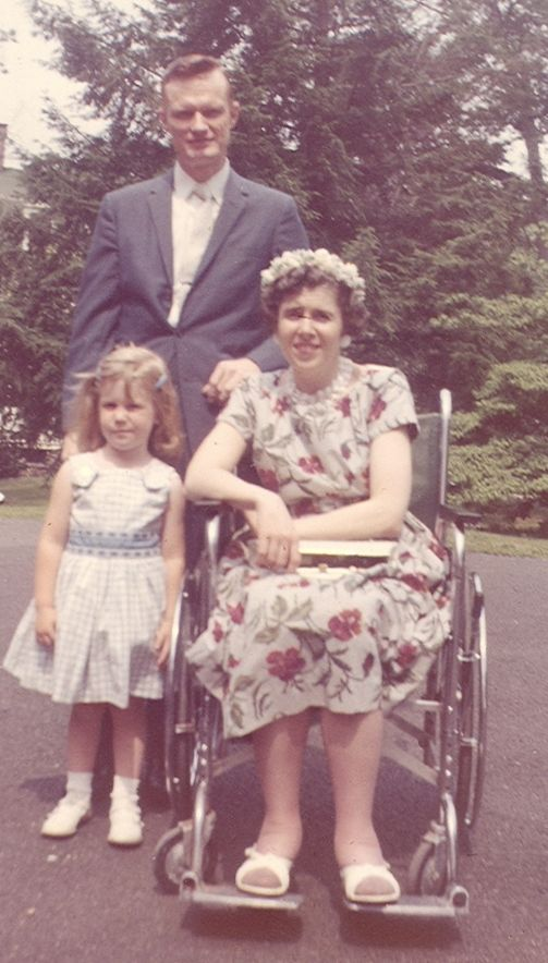 Author as little girl stand next to her mother iwho is in a wheelchair - the father stands behind them.  They are all dressed in Sunday best for the 1950_s