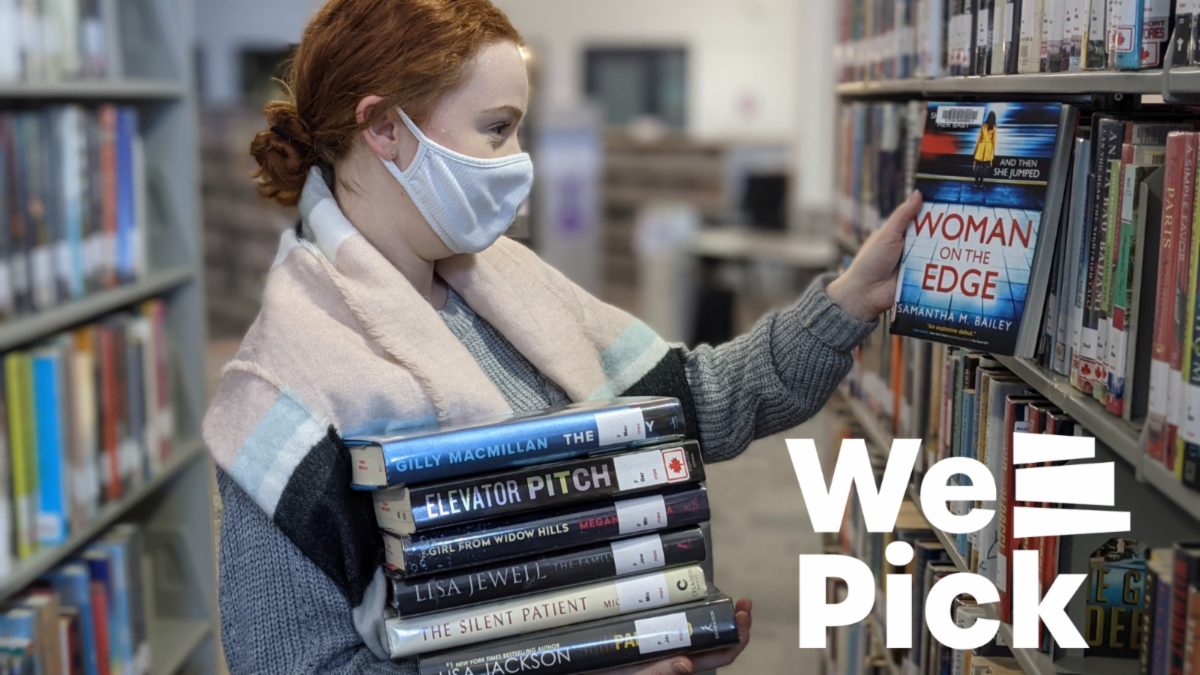 Photo of Library staff person choosing a book from the shelf while holding a stock of books. We Pick logo layered over photo.