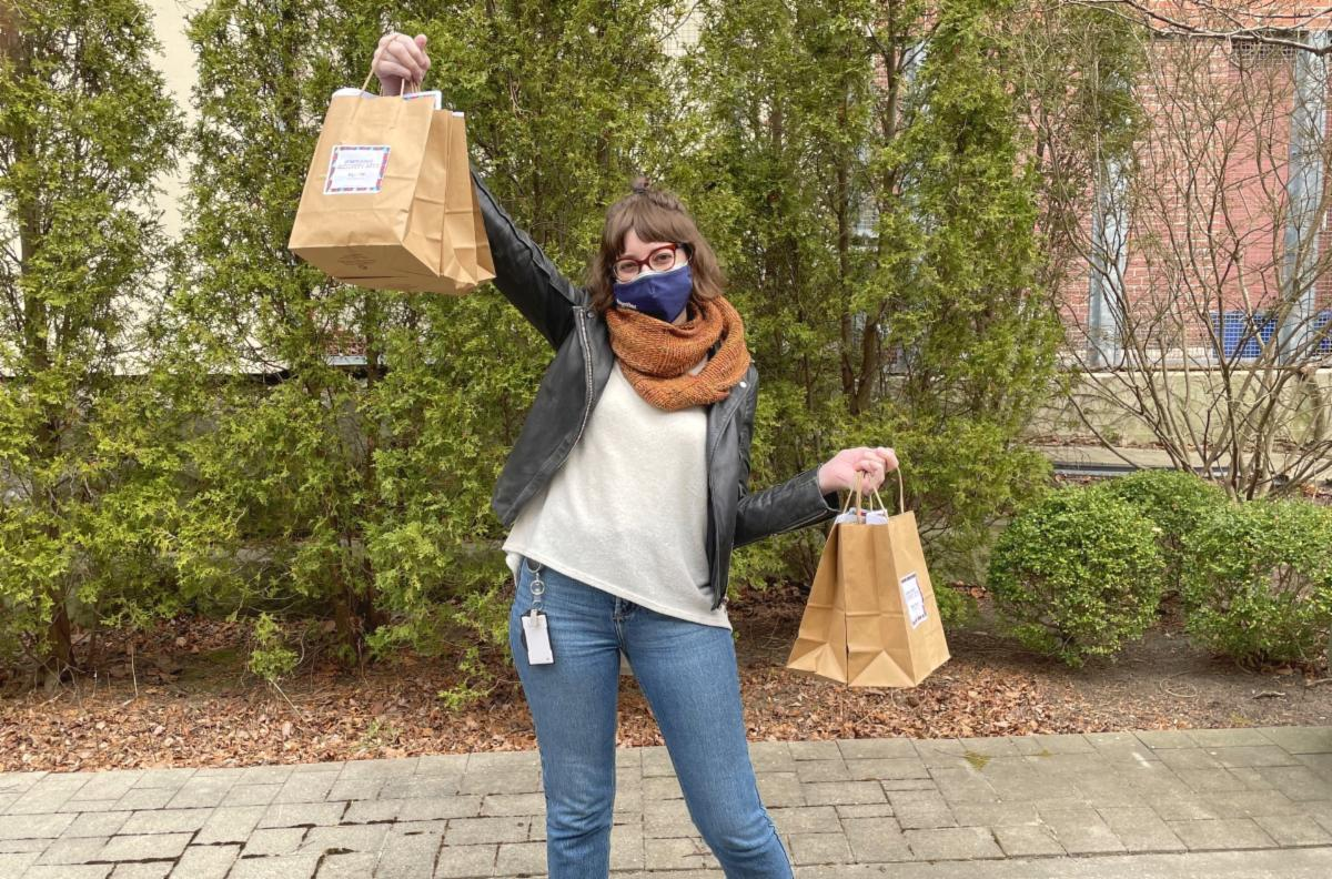Library staff person wearing a mask and standing outside holding Spring Break Activity Kits in paper bags.