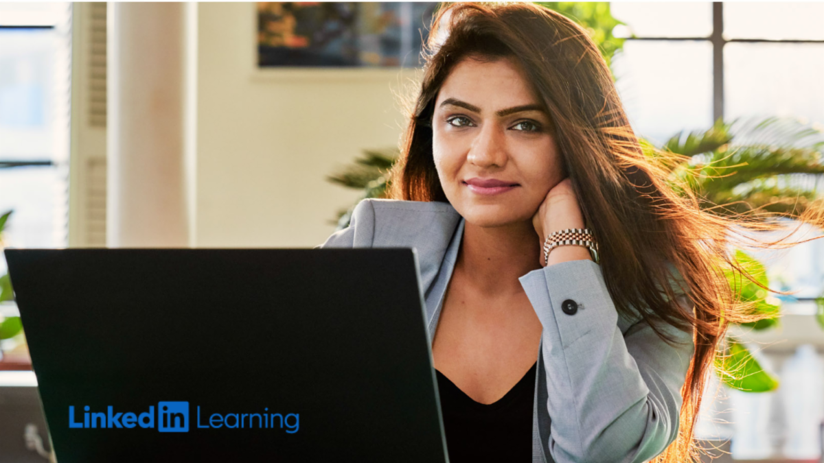 Photo of young woman in a blazer sitting at a laptop with a Linkedin Learning logo.