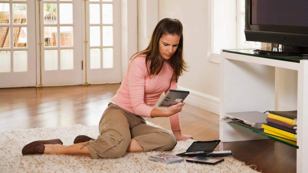 woman at home looking at dvd covers beside a television set