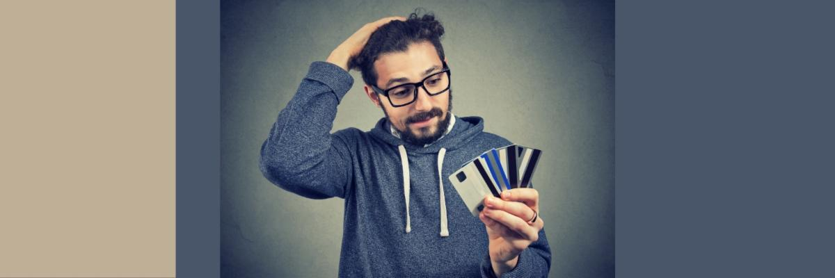 Photo illustration of young male in glasses and a sweatshirt holding multiple credit cards and running his hand through his hair, looking stressed.