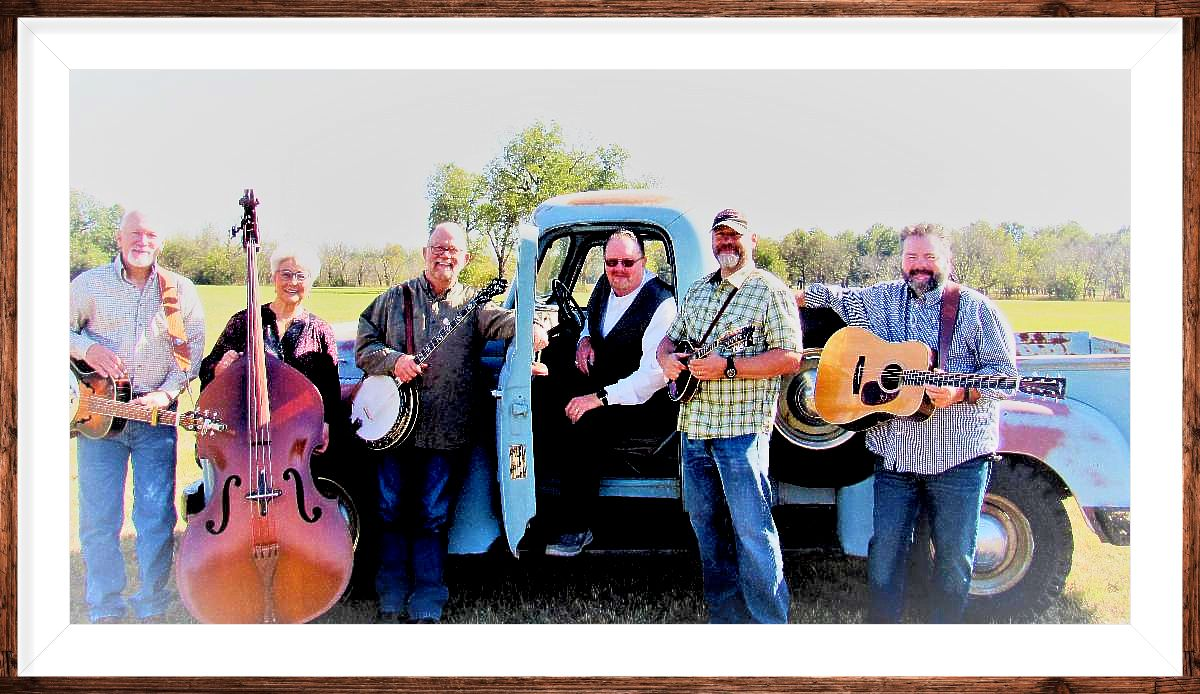The Roving Gambler band with instruments in front of a vintage blue pickup at the Tallgrass Music Festival in 2020